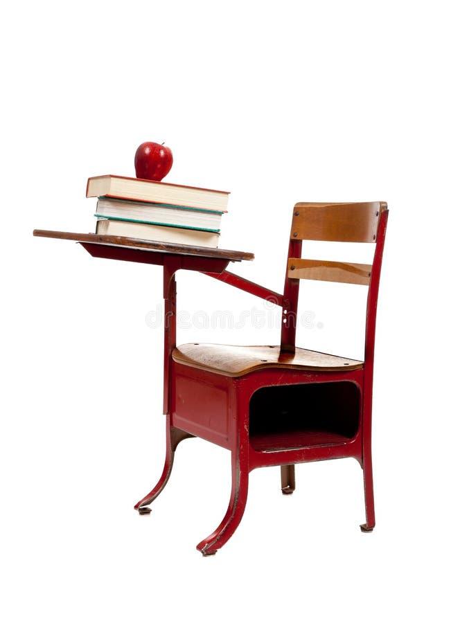 Escritorio rojo de la escuela con los libros en blanco imagen de archivo libre de regalías