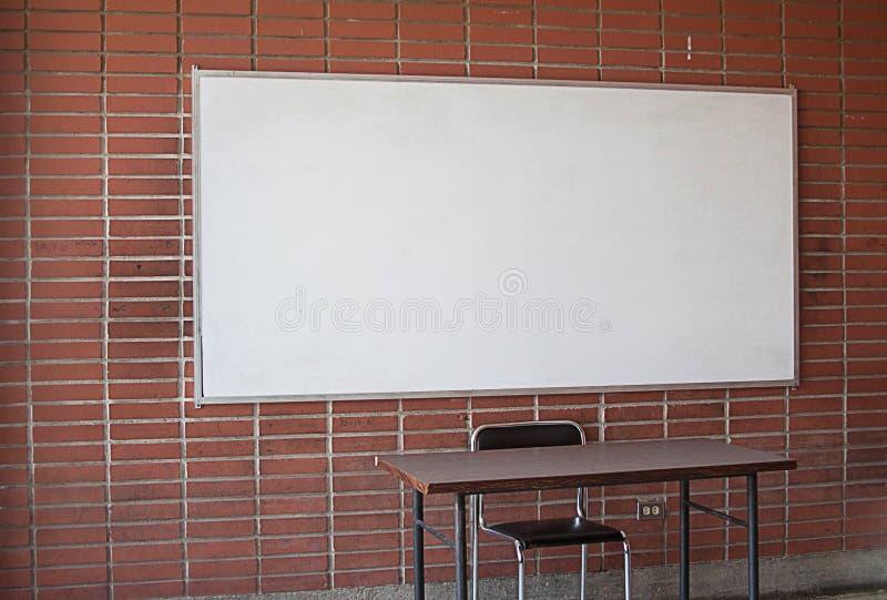 Escritorio vacío del ` s del profesor en una sala de clase imagen de archivo
