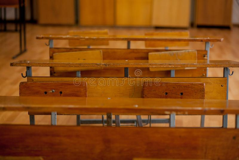 Escritorios de madera de la escuela del viejo vintage en sala de clase foto de archivo