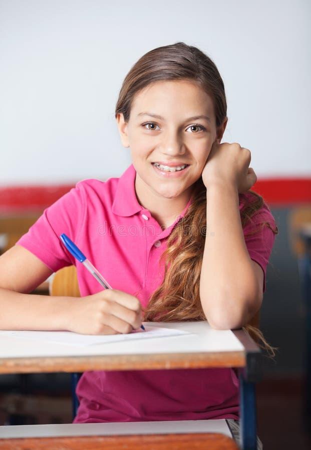 Escritura adolescente de la colegiala en el escritorio imagen de archivo