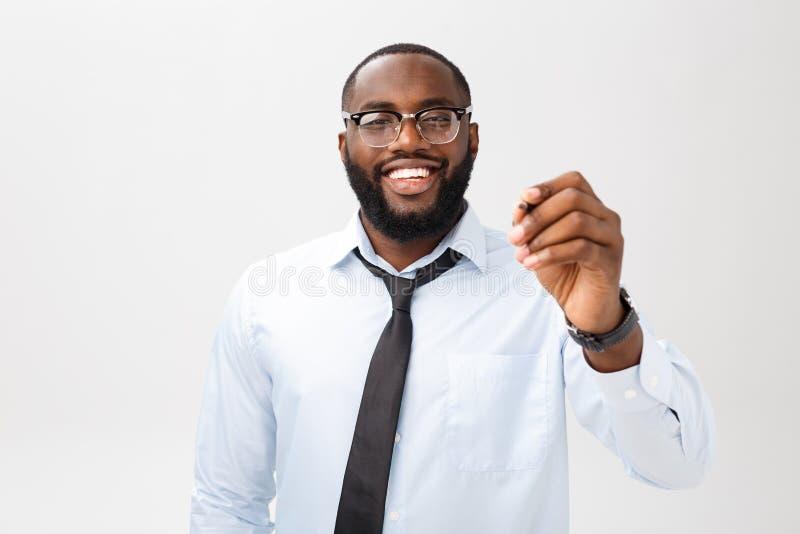 Escritura afroamericana joven del hombre de negocios algo en el tablero de cristal con un marcador fotos de archivo