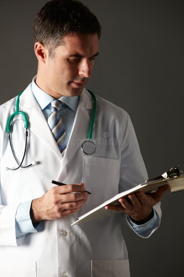 Escritura americana del doctor en su sujetapapeles imágenes de archivo libres de regalías