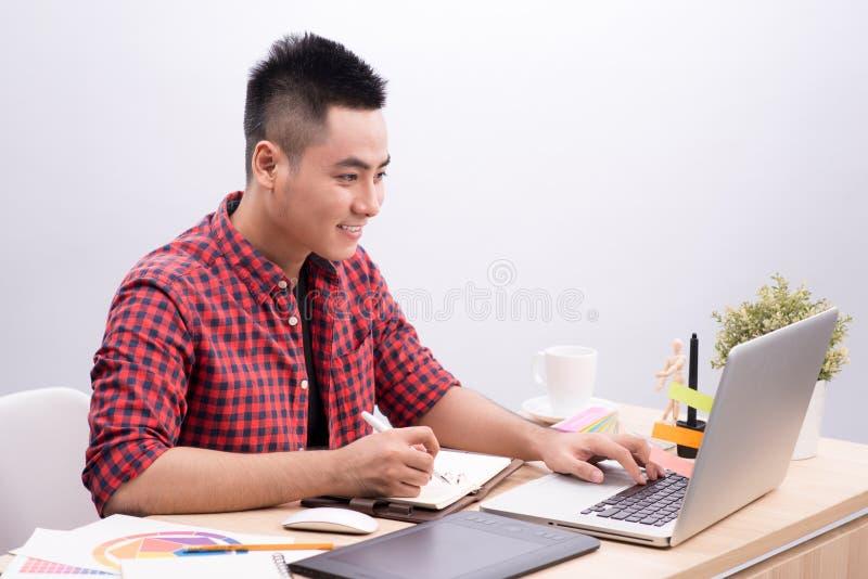 Escritura asiática del hombre en el escritorio en oficina creativa ocupada fotos de archivo