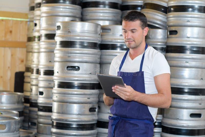 Escritura atenta del trabajador del mantenimiento en el tablero en la cervecería foto de archivo