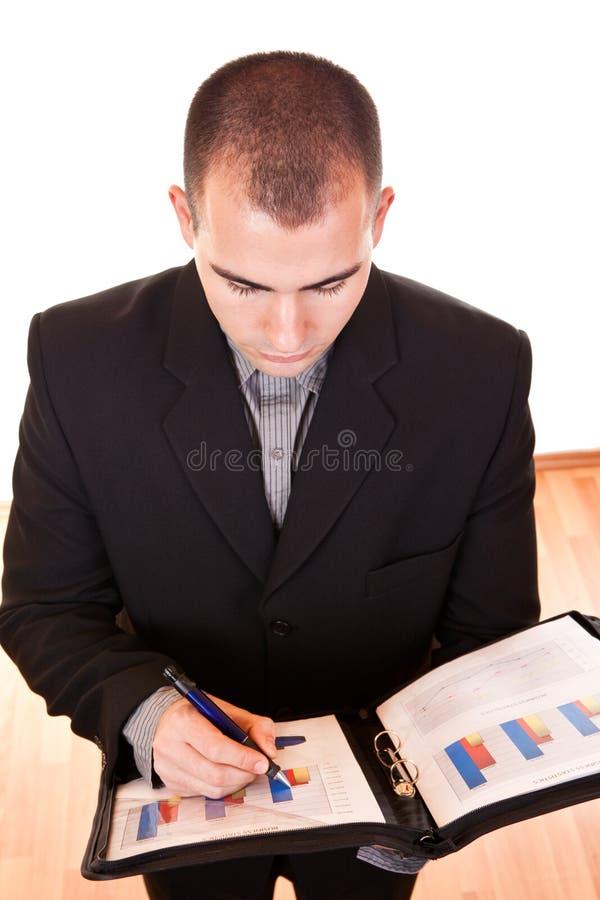 Escritura atractiva del hombre de negocios en documentos foto de archivo libre de regalías
