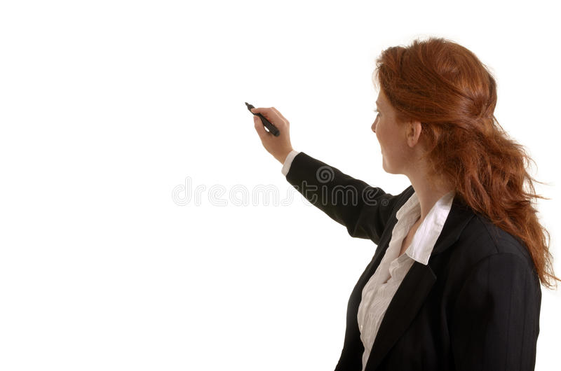 Escritura bastante pelirroja de la mujer de negocios con la pluma foto de archivo