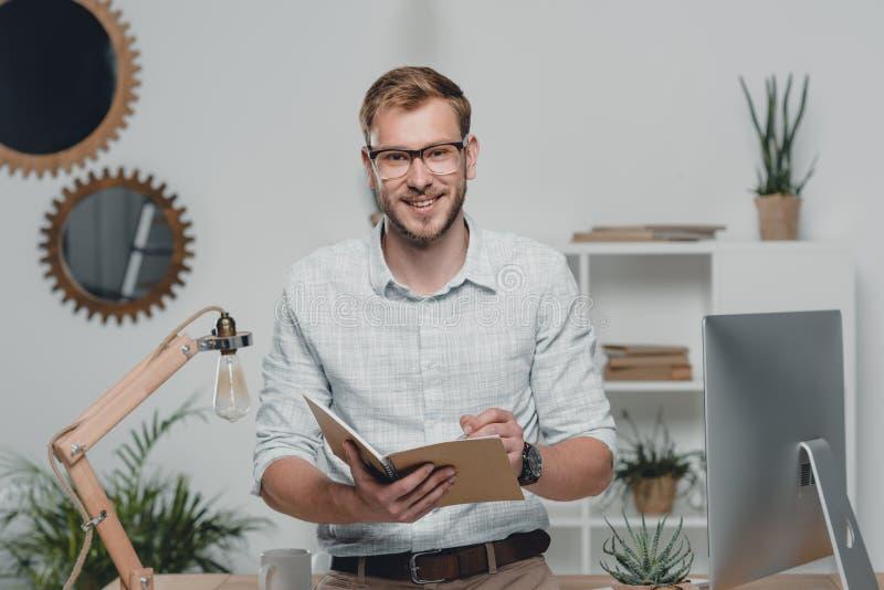 Escritura caucásica del hombre de negocios en diario y sonrisa en la cámara en oficina moderna foto de archivo