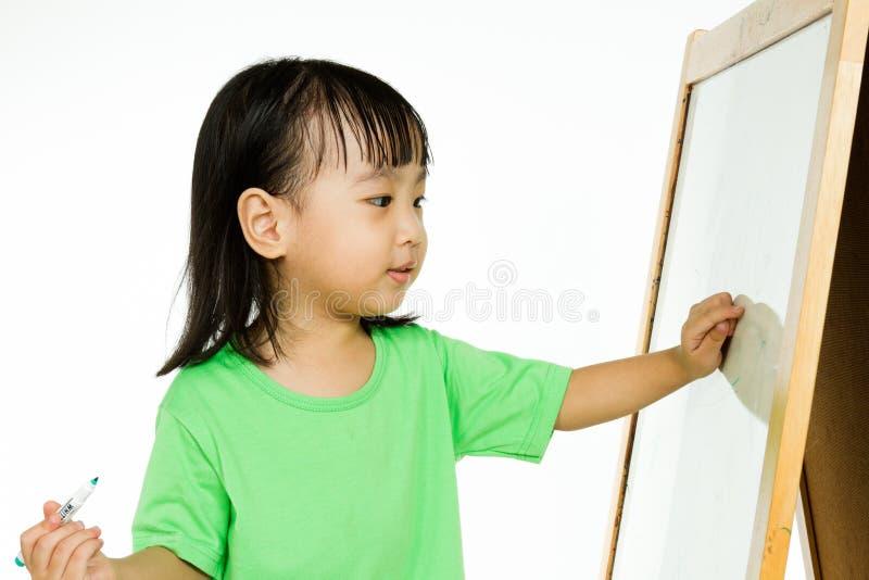 Escritura china de la niña en whiteboard fotografía de archivo libre de regalías