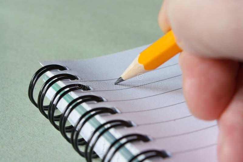 Escritura con un lápiz amarillo fotos de archivo libres de regalías