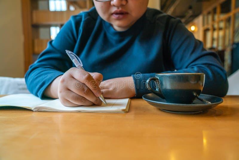Escritura de la chica joven en su cuaderno foto de archivo