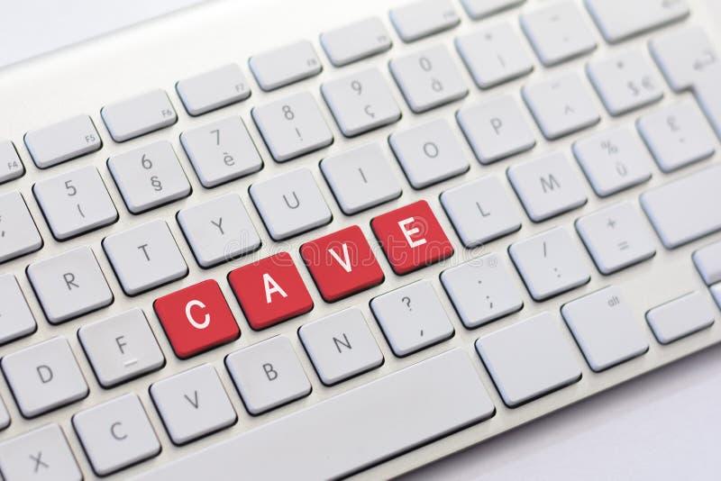 Escritura de la CUEVA en el teclado blanco imagen de archivo libre de regalías