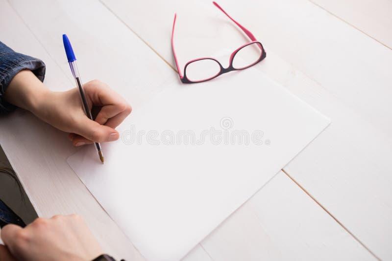 Escritura de la empresaria en la hoja de papel imagen de archivo