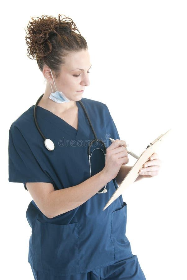 Escritura de la enfermera en un sujetapapeles foto de archivo libre de regalías