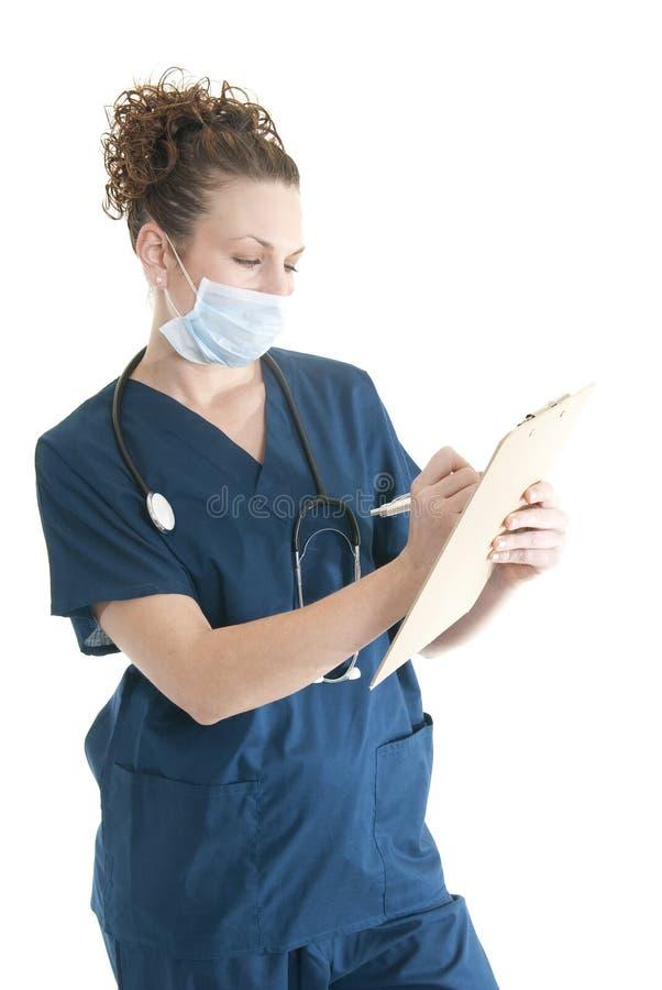Escritura de la enfermera en un sujetapapeles fotografía de archivo