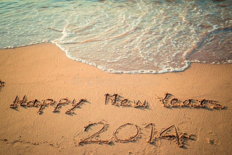 Escritura de la Feliz Año Nuevo 2014 en la playa imágenes de archivo libres de regalías
