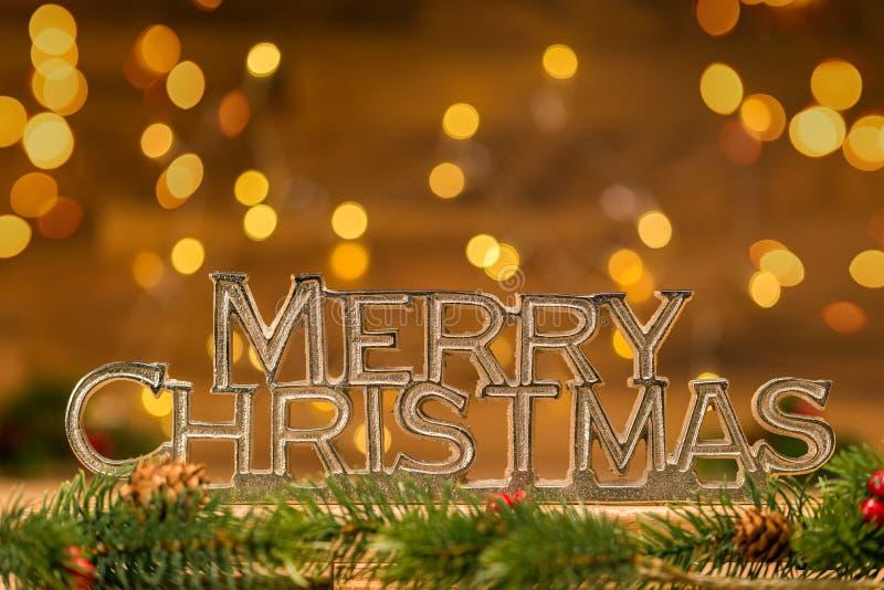 Escritura de la Feliz Navidad con la rama del abeto en frente y el bokeh en vagos foto de archivo libre de regalías