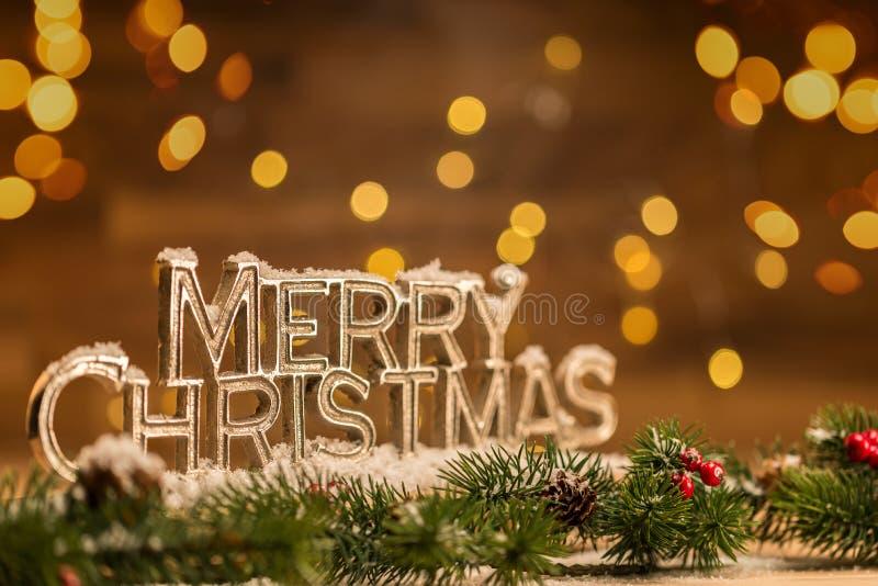 Escritura de la Feliz Navidad con la rama nevosa del abeto en frente y bokeh imagen de archivo libre de regalías