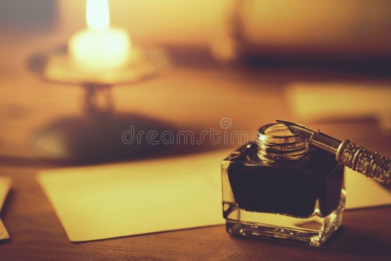 Escritura de la letra con la pluma de canilla y de la tinta en luz de una vela imágenes de archivo libres de regalías