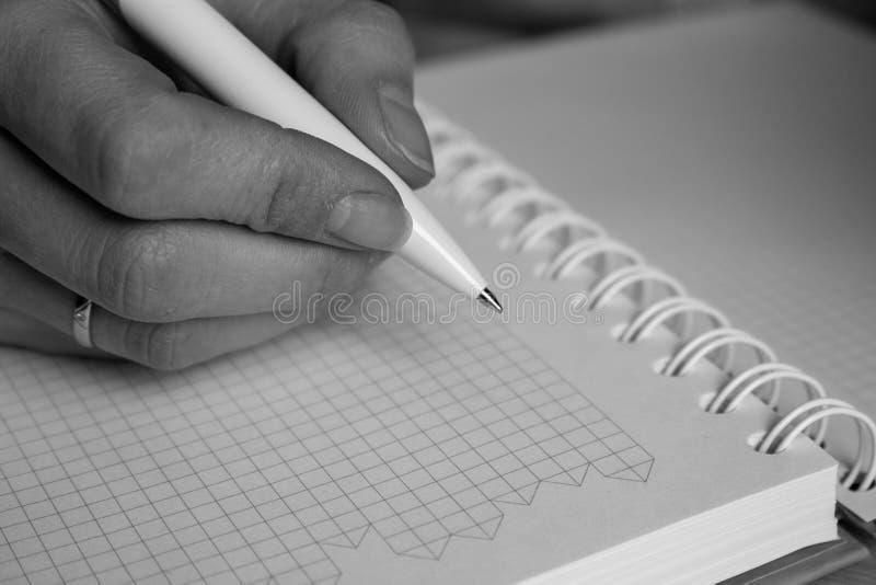 Escritura de la mano con la pluma en cuaderno en cierre de la célula encima del monocromo Negocio y concepto de la oficina Concep fotografía de archivo libre de regalías