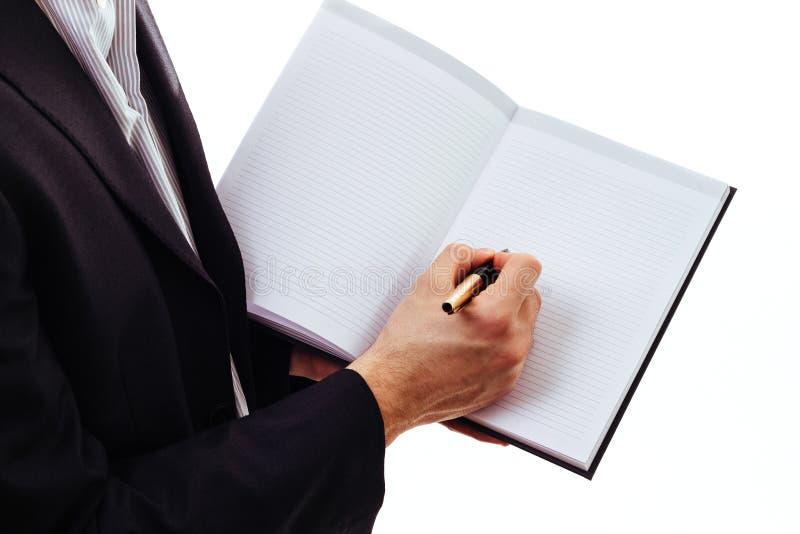 Escritura de la mano del hombre de negocios con la pluma fotos de archivo