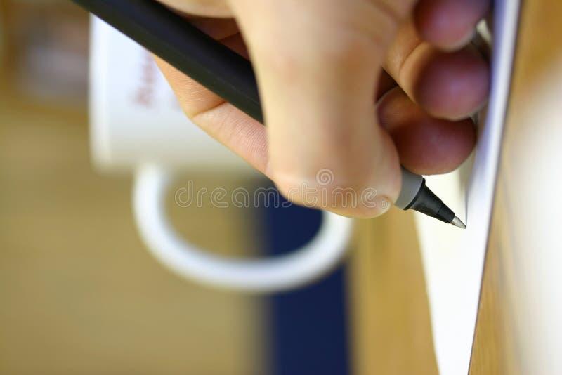 Escritura de la mano del hombre en el escritorio foto de archivo