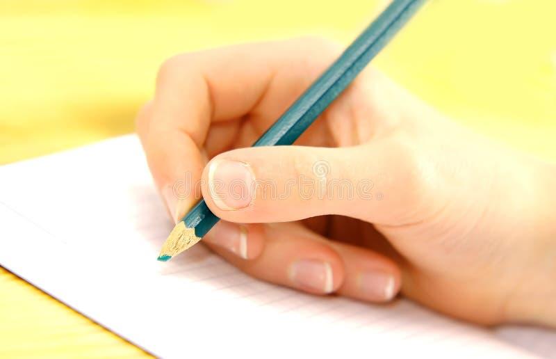 Escritura de la mano del niño foto de archivo