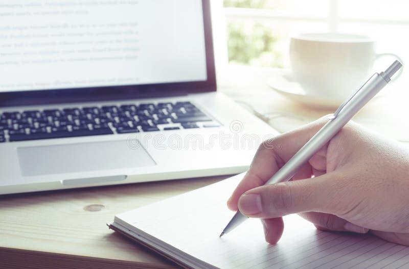 Escritura de la mano en el cuaderno con el ordenador portátil Momento de la inspiración imágenes de archivo libres de regalías