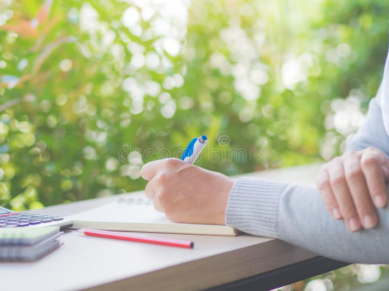 Escritura de la mano de la mujer con la pluma blanca, el lápiz rojo y la calculadora fotografía de archivo libre de regalías