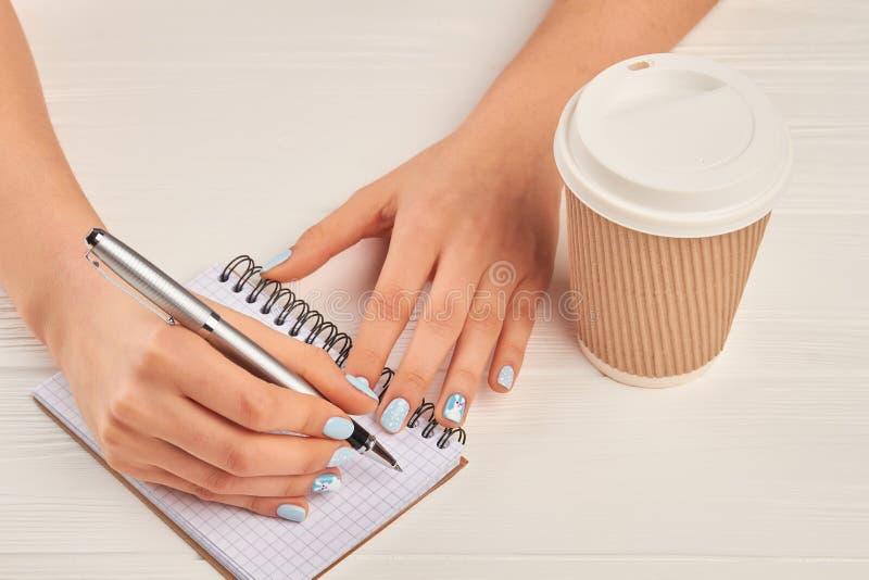 Escritura de la mano de la mujer en el cuaderno foto de archivo