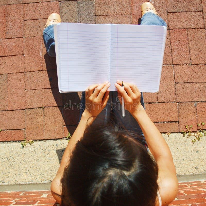 Escritura de la muchacha en cuaderno foto de archivo libre de regalías
