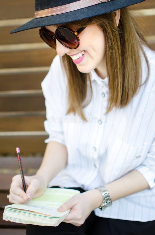 Escritura de la muchacha en un banco fotos de archivo