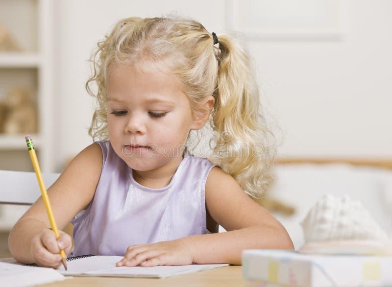 Escritura de la muchacha en un cuaderno foto de archivo