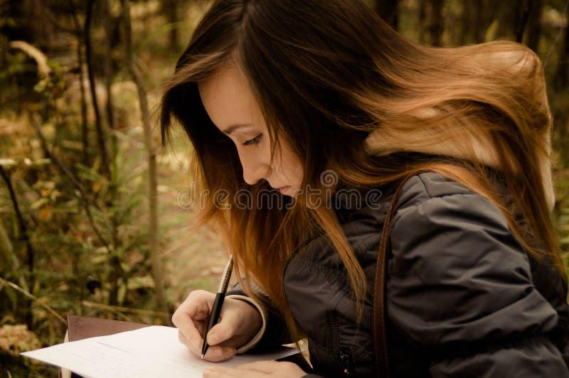 Escritura de la muchacha roja en el bosque foto de archivo