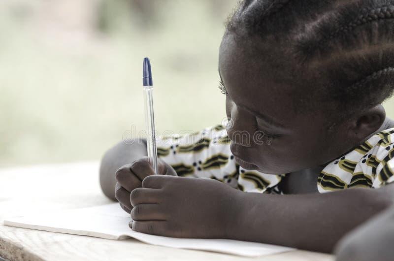 Escritura de la muchacha y actividad de aprendizaje negras hermosas con un p azul imagen de archivo