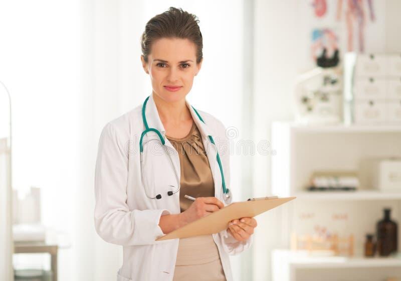 Escritura de la mujer del médico en tablero foto de archivo libre de regalías