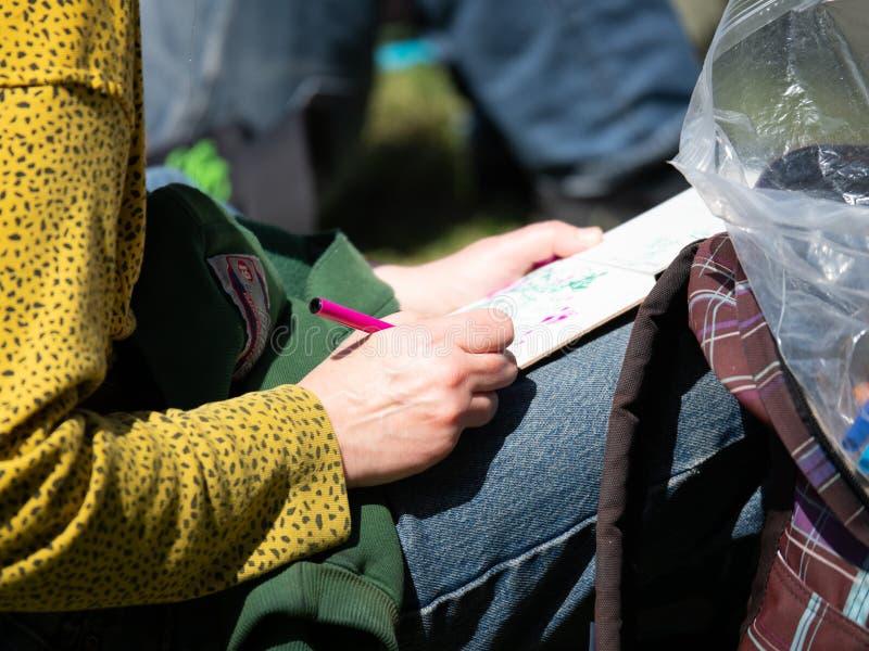 Escritura de la mujer en diario con la pluma roja imagenes de archivo