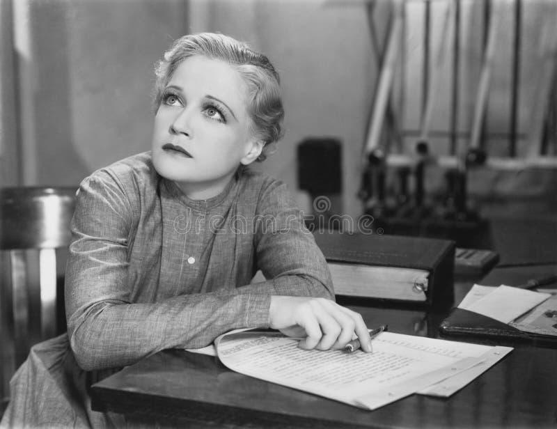 Escritura de la mujer en el escritorio fotos de archivo
