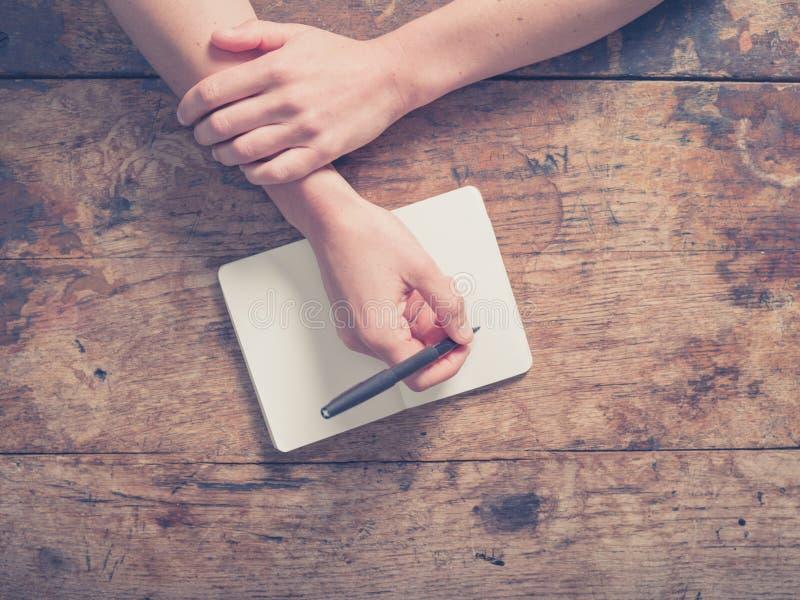 Escritura de la mujer en libreta en la tabla de madera imagenes de archivo