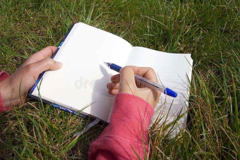 Escritura de la mujer en un libro en blanco foto de archivo libre de regalías