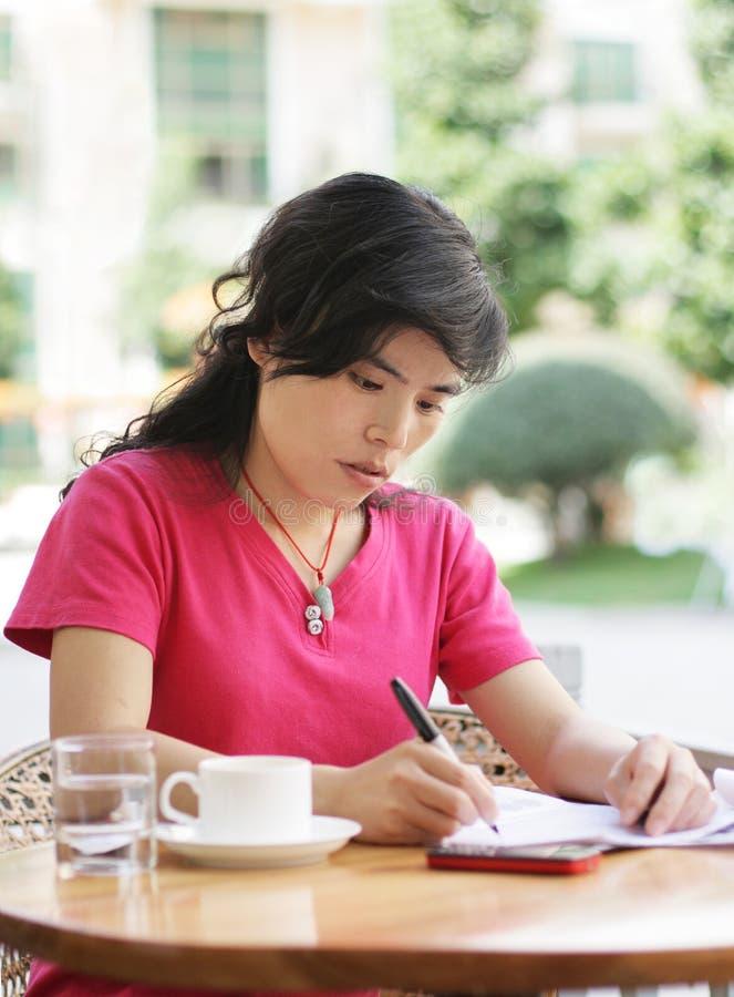 Escritura de la mujer en una hoja del papel imagen de archivo