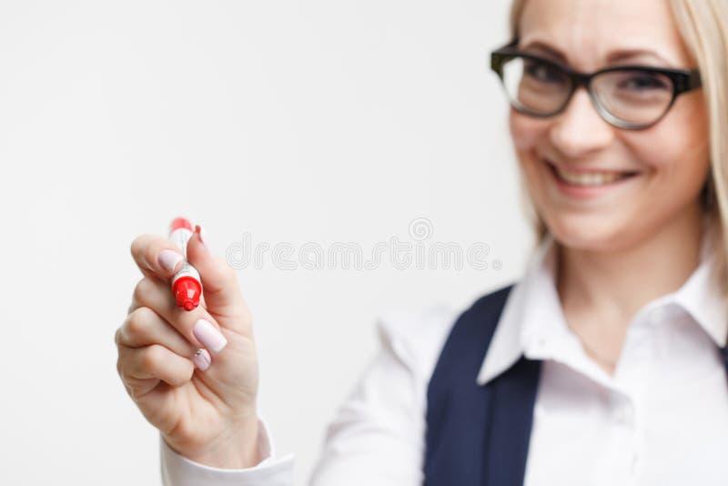 Escritura de la mujer de negocios algo con un marcador o una pluma fotografía de archivo