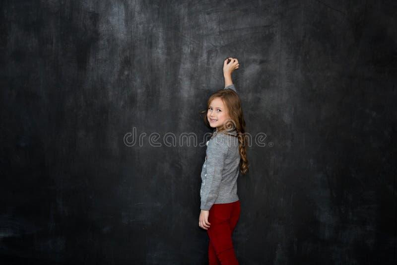 Escritura de la niña algo con una tiza en la pizarra fotografía de archivo libre de regalías