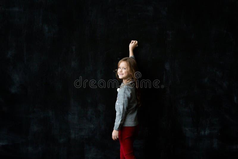Escritura de la niña algo con una tiza en la pizarra imagenes de archivo