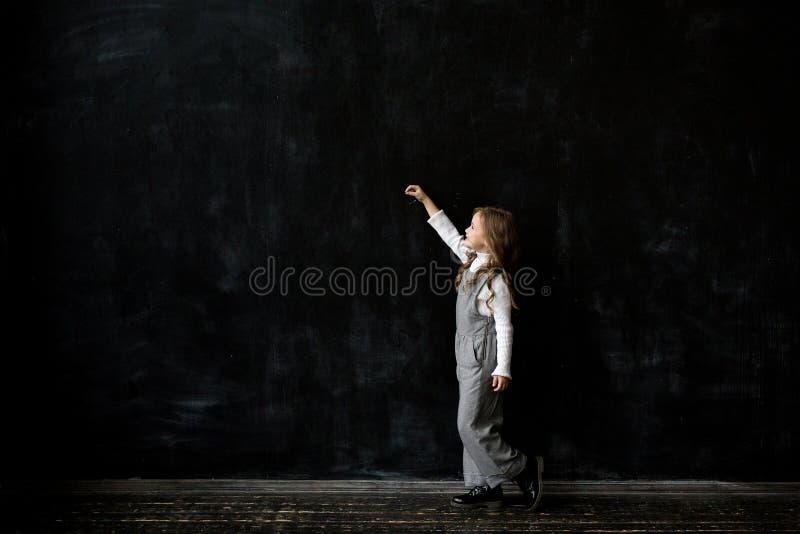 Escritura de la niña algo con una tiza en la pizarra fotos de archivo libres de regalías