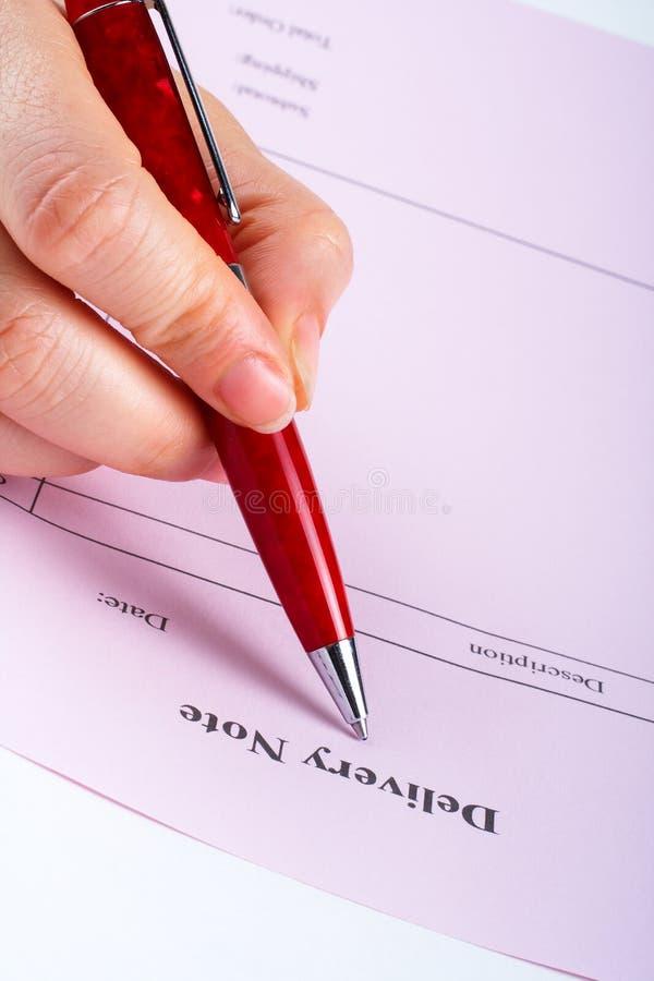 Escritura de la nota de salida en blanco con la pluma imagen de archivo libre de regalías