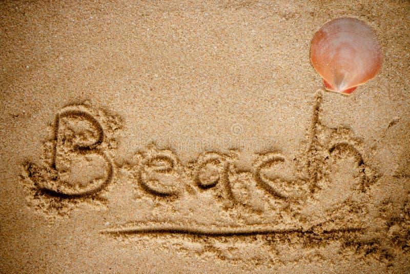 Escritura de la playa de la palabra en la playa de la arena imagen de archivo