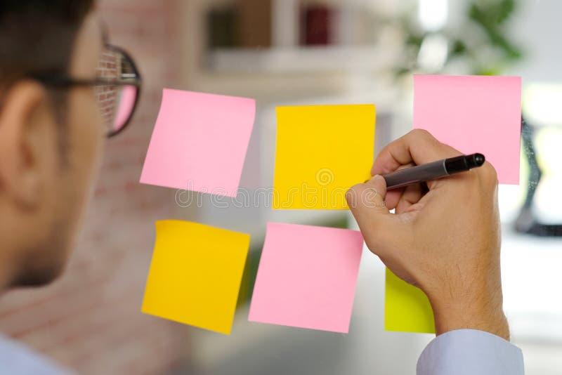Escritura de la pluma de tenencia de la mano en los papeles de nota pegajosos coloridos en blanco en el tablero de cristal en la  foto de archivo libre de regalías
