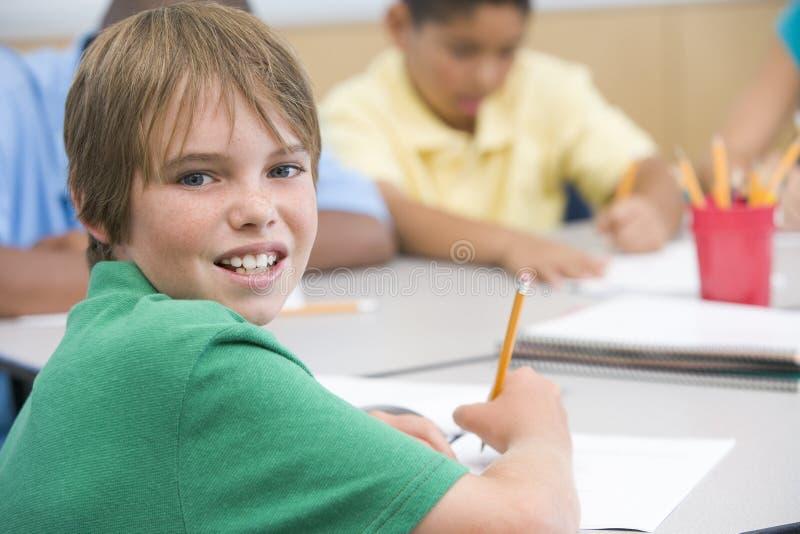 Escritura de la pupila de la escuela primaria imagen de archivo