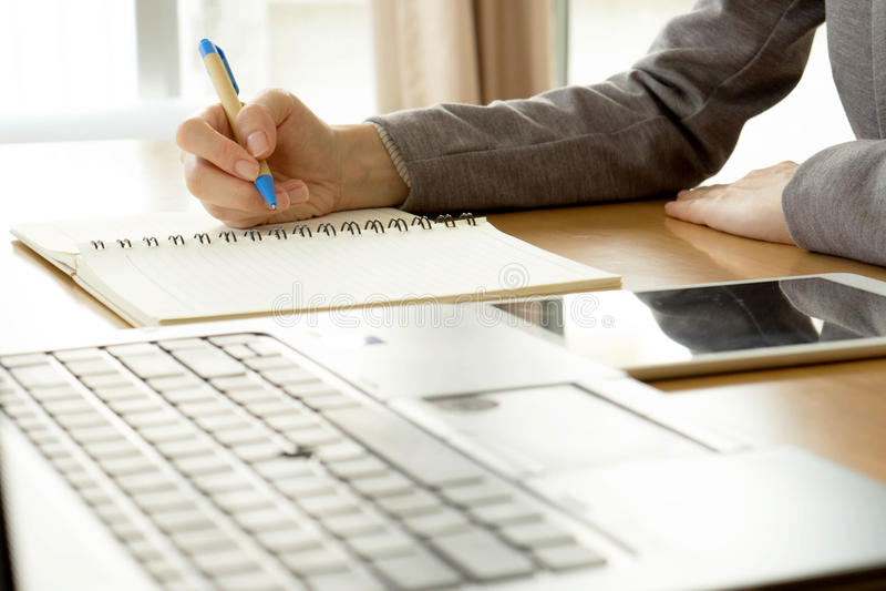 Escritura de la trabajadora en el papel y el mecanografiar en COM del ordenador portátil fotografía de archivo
