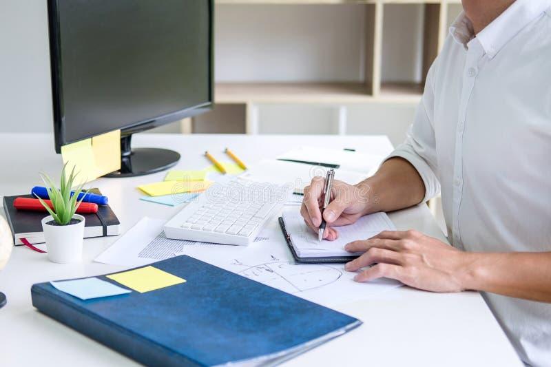 Escritura de trabajo del hombre de negocios que hace el plan empresarial de la nota y al dise?ador gr?fico con el ordenador en of imagen de archivo
